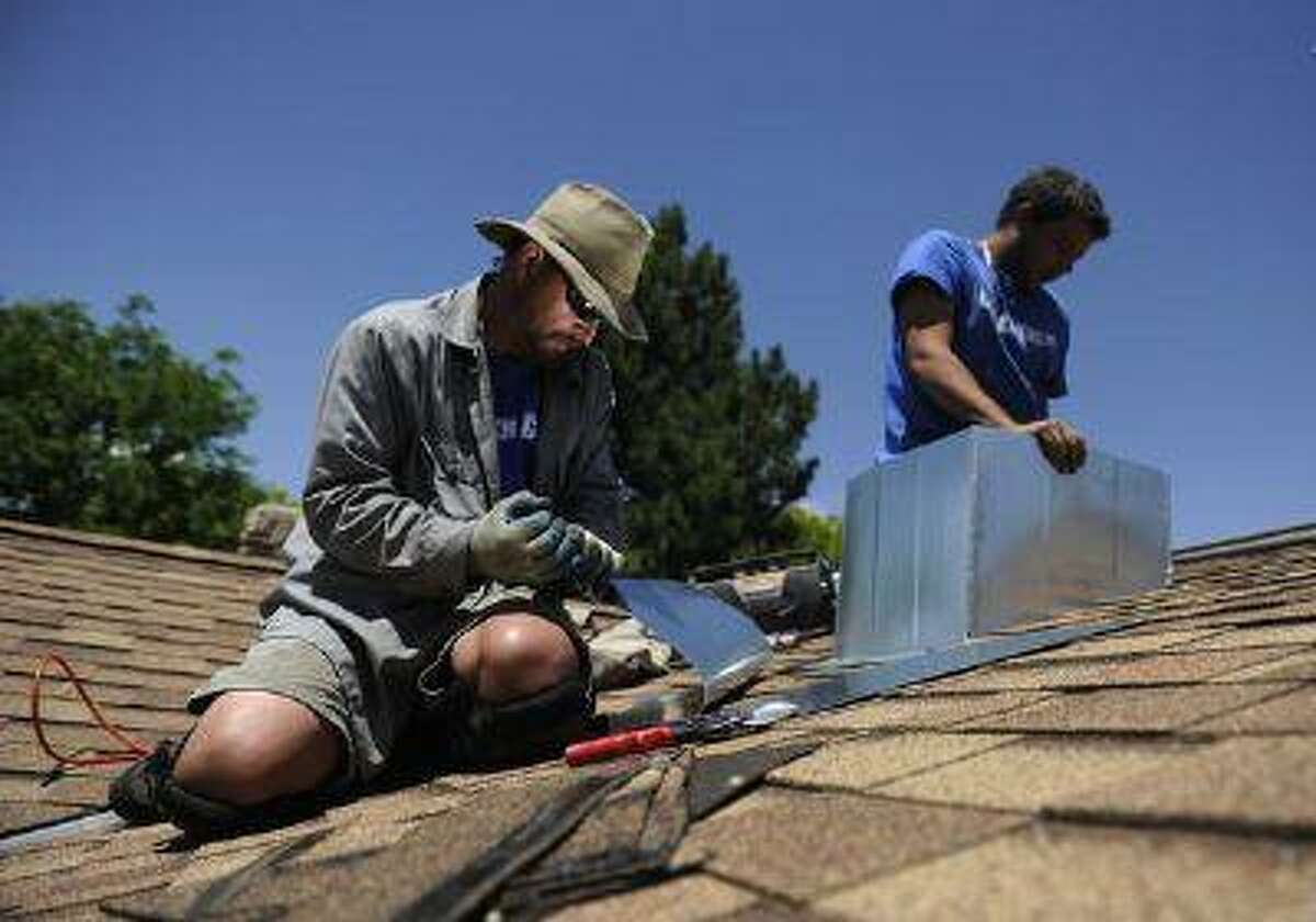 Foreman Tim Steele of The Cooler Company installs a Breezair evaporative cooler on the roof of a home as his colleague Bowen Christensen climbs into the attic.