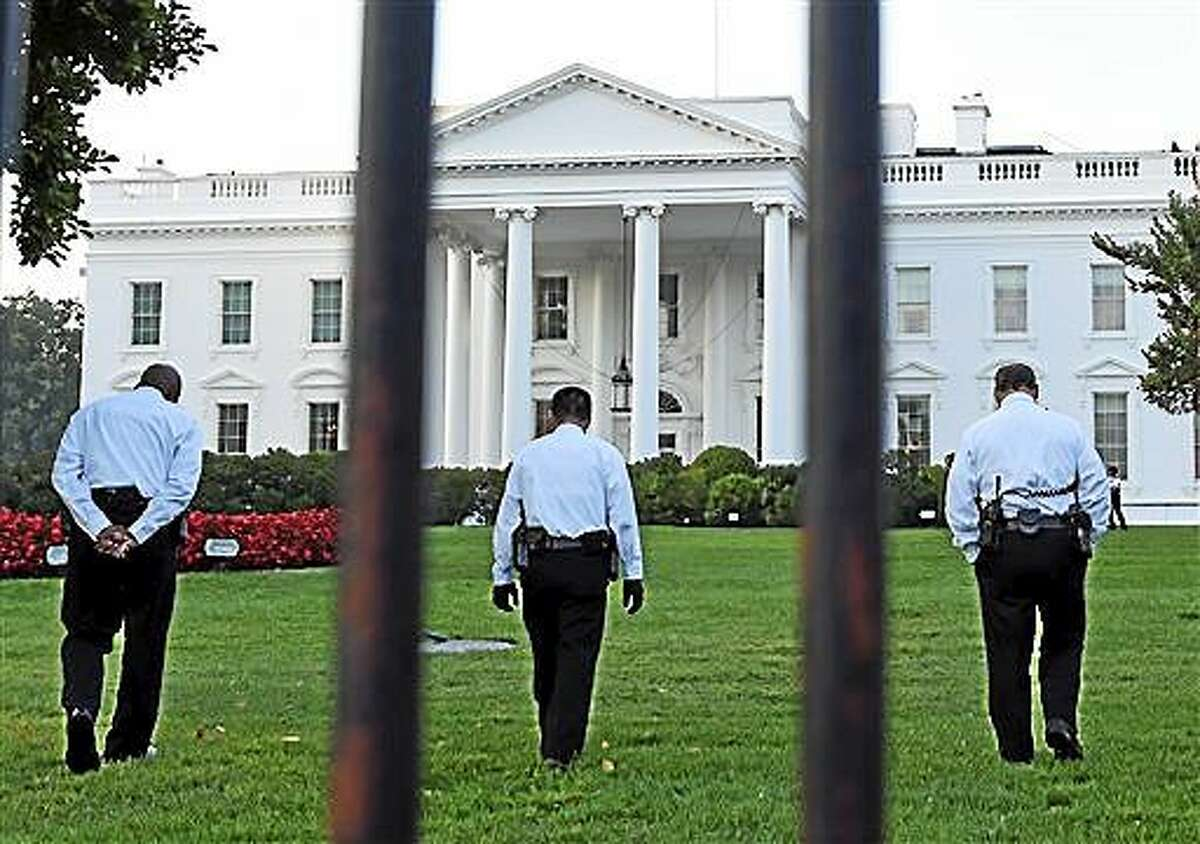 Uniformed Secret Service officers walk along the lawn on the North side of the White House in Washington, Saturday, Sept. 20, 2014. The Secret Service is coming under renewed scrutiny after a man scaled the White House fence and made it all the way through the front door before he was apprehended. (AP Photo/Susan Walsh)