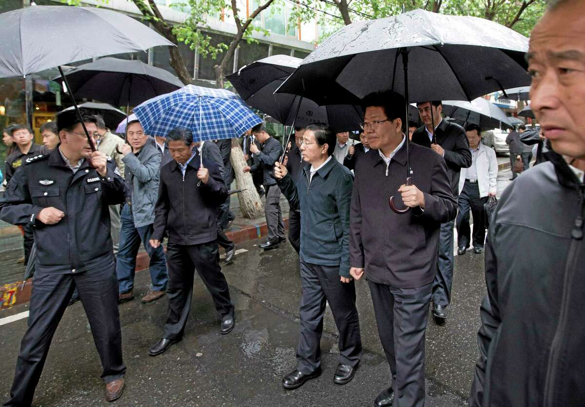 China's Public Security Minister Guo Shengkun, center, and Xinjiang Party Secretary Zhang Chunxian, second right, hold umbrellas as they visit the site of an explosion in Urumqi, northwestern China's Xinjiang region, Thursday, May 22, 2014. Assailants in two SUVs plowed through shoppers while setting off explosives on a busy street market in China's volatile region of Xinjiang on Thursday, the local officials said, killing over two dozen people and injuring more than 90. The attack was the bloodiest in a series of violent incidents that Chinese authorities have blamed on radical separatists from the country's Muslim Uighur minority. (AP Photo/Andy Wong)