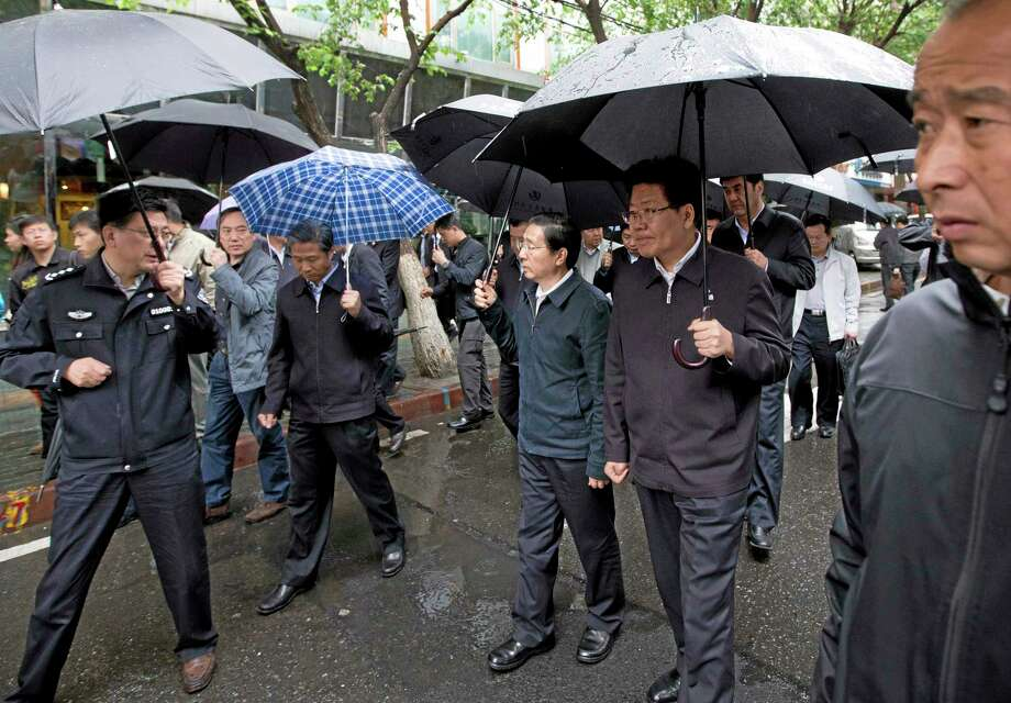 China's Public Security Minister Guo Shengkun, center, and Xinjiang Party Secretary Zhang Chunxian, second right, hold umbrellas as they visit the site of an explosion in Urumqi, northwestern China's Xinjiang region, Thursday, May 22, 2014. Assailants in two SUVs plowed through shoppers while setting off explosives on a busy street market in China's volatile region of Xinjiang on Thursday, the local officials said, killing over two dozen people and injuring more than 90. The attack was the bloodiest in a series of violent incidents that Chinese authorities have blamed on radical separatists from the country's Muslim Uighur minority. (AP Photo/Andy Wong) Photo: AP / AP
