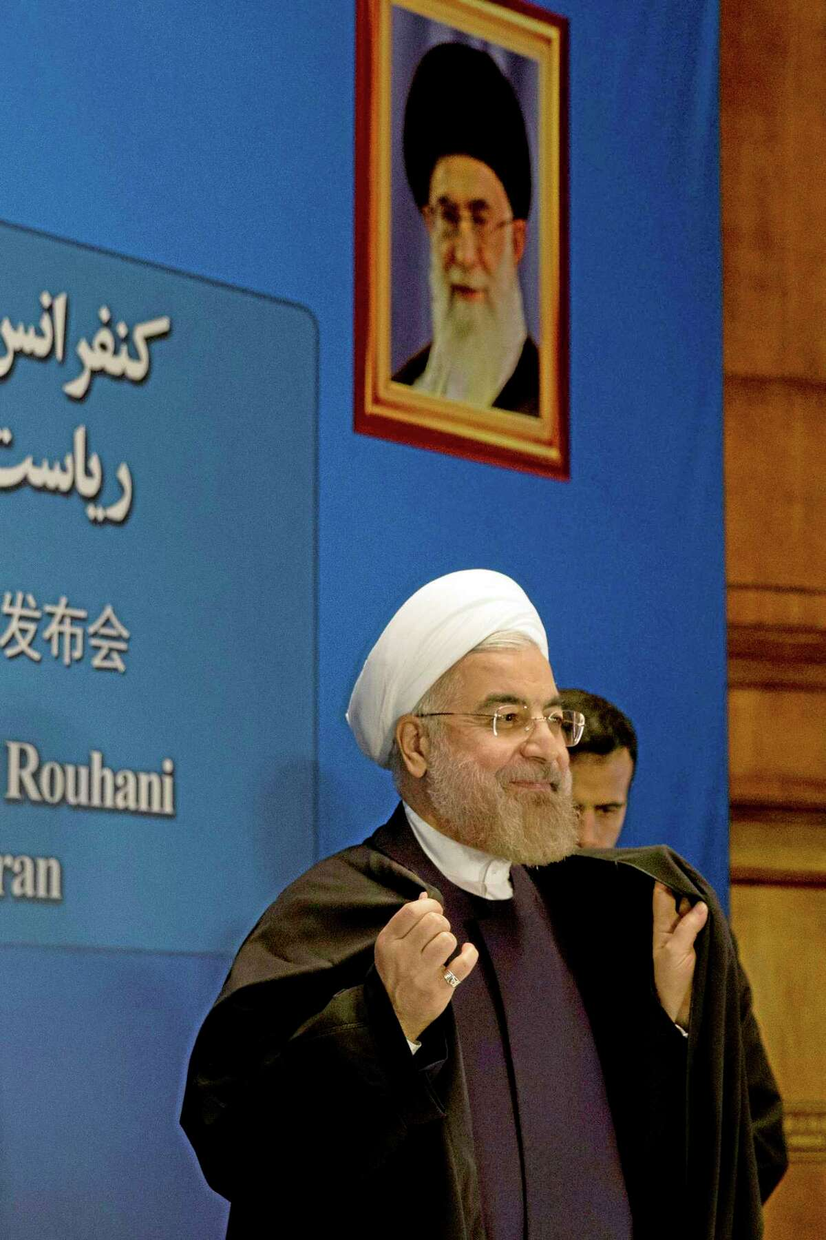 Iranian President Hassan Rouhani prepares to leave after a press conference near a portrait of Iranian Supreme Leader Ayatollah Ali Khamenei at a hotel in Shanghai, China, Thursday, May 22, 2014. Rouhani says an agreement on curbing its nuclear program is