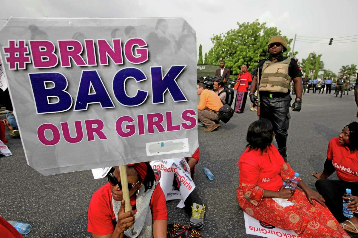 A police officer stands guard as people attend a demonstration calling on the government to rescue the kidnapped girls of the government secondary school in Chibok, in Abuja, Nigeria, Thursday, May 22, 2014. Scores of protesters chanting