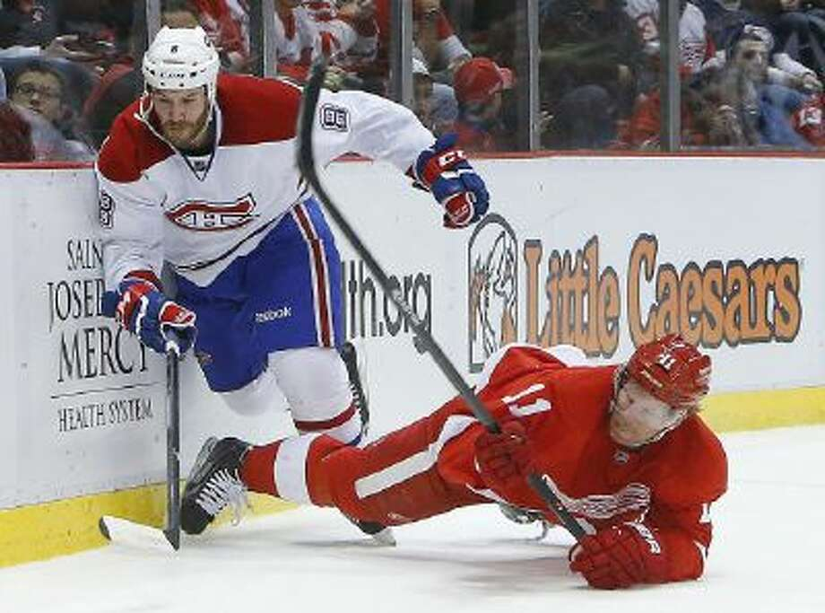 Detroit Red Wings right wing Daniel Alfredsson (11), of Sweden, is taken down by Montreal Canadiens right wing Brandon Prust (8) during a game Jan. 24 in Detroit.
