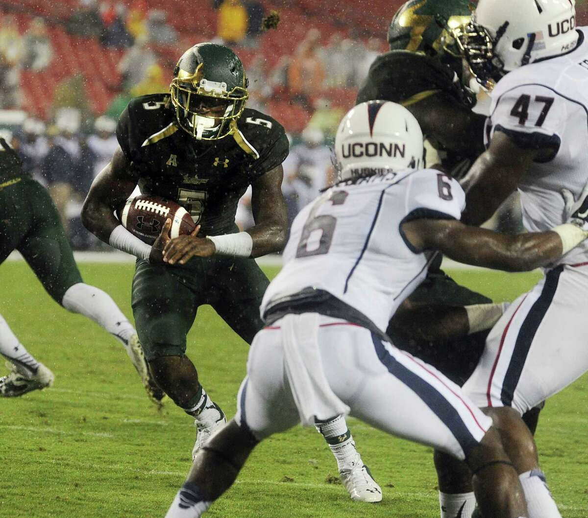 The University of South Florida's Marlon Mack (5) finds running room on his way to a touchdown against UConn during the Bulls' 17-14 win on Friday night in Tampa, Fla.
