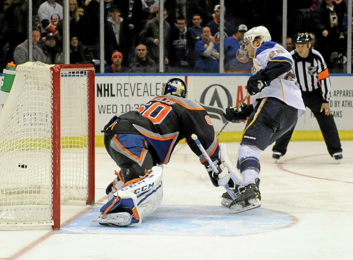 St. Louis Blues defensman Kevin Shattenkirk, right, shoots the puck past New York Islanders goalie Kevin Poulin to score the winning goal during a shootout on Saturday in Uniondale, N.Y.