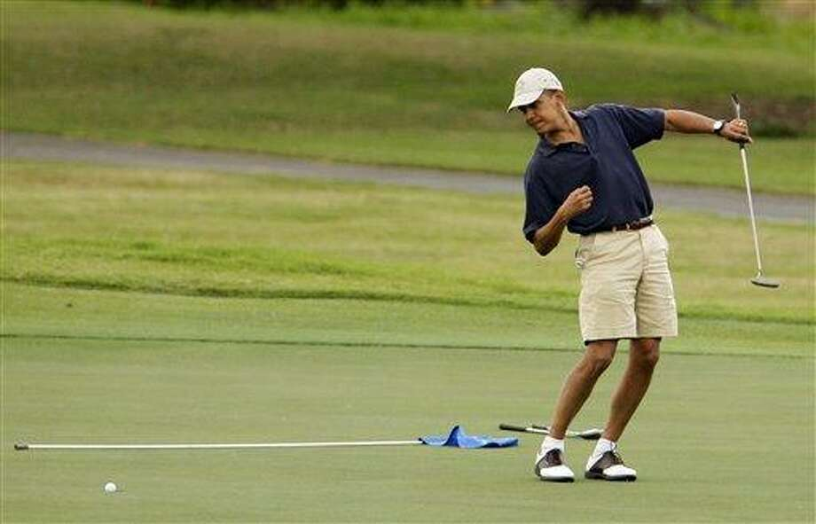 , President Barack Obama watches the ball after making a putt on the ninth green during his golf match at Mid-Pacific County Club in Kailua, Hawaii. Obama played golf Sunday with Tiger Woods, the White House said Sunday. Once the sport's dominant player before his career was sidetracked by scandal, Woods joined Obama at the Floridian, a secluded and exclusive yacht and golf club on Florida's Treasure Coast where Obama is spending the long Presidents Day weekend. The two had met before, but Sunday was the first time they played together. AP Photo/Chris Carlson Photo: ASSOCIATED PRESS / A2009