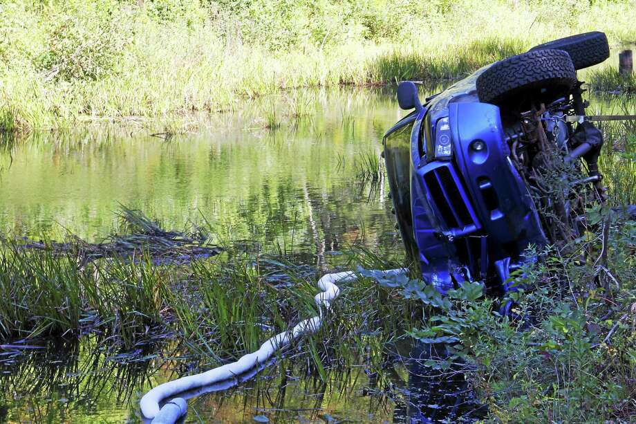 A pick up truck sits inside a pond on Winsted Road after striking a utility pole Friday in Torrington. The driver of the car suffered minor injuries. Photo: Esteban L. Hernandez  — The Register Citizen