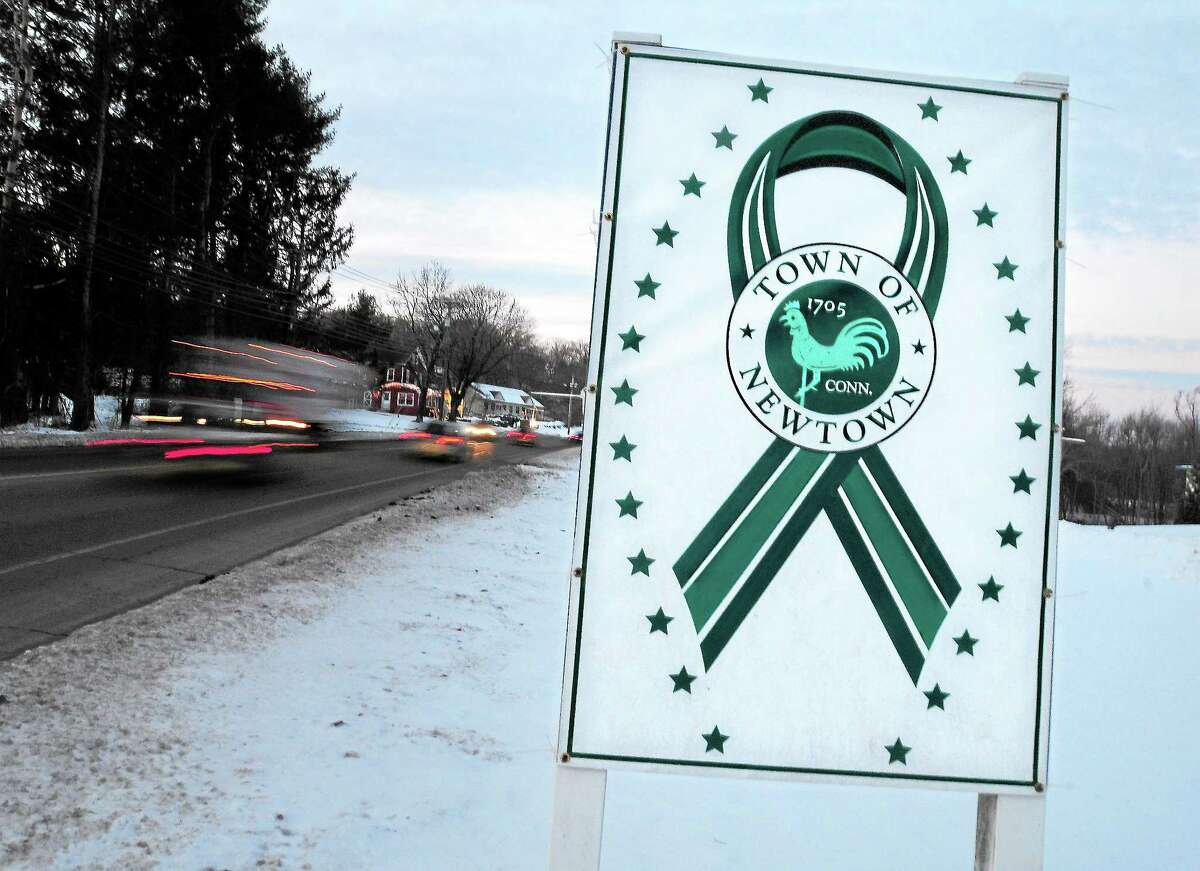 A sign with a green ribbon surrounded by 26 stars remains on South Main St. in Newtown on 1/4/2013.