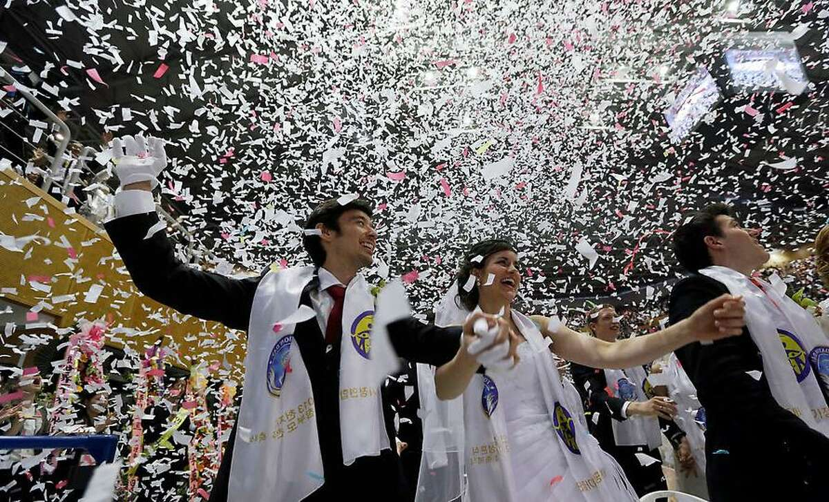Natalia Ladstaotter, from Austria, center, and her groom Colin Brouard, from England, left, cheer during a mass wedding ceremony at the CheongShim Peace World Center in Gapyeong, South Korea, Sunday, Feb. 17, 2013. Some 3,500 South Korean and foreign couples exchanged or reaffirmed marriage vows in the Unification Church's mass wedding arranged by Hak Ja Han Moon, the second wife of the late Rev. Sun Myung Moon, the controversial founder of the Unification Church. (AP Photo/Lee Jin-man)