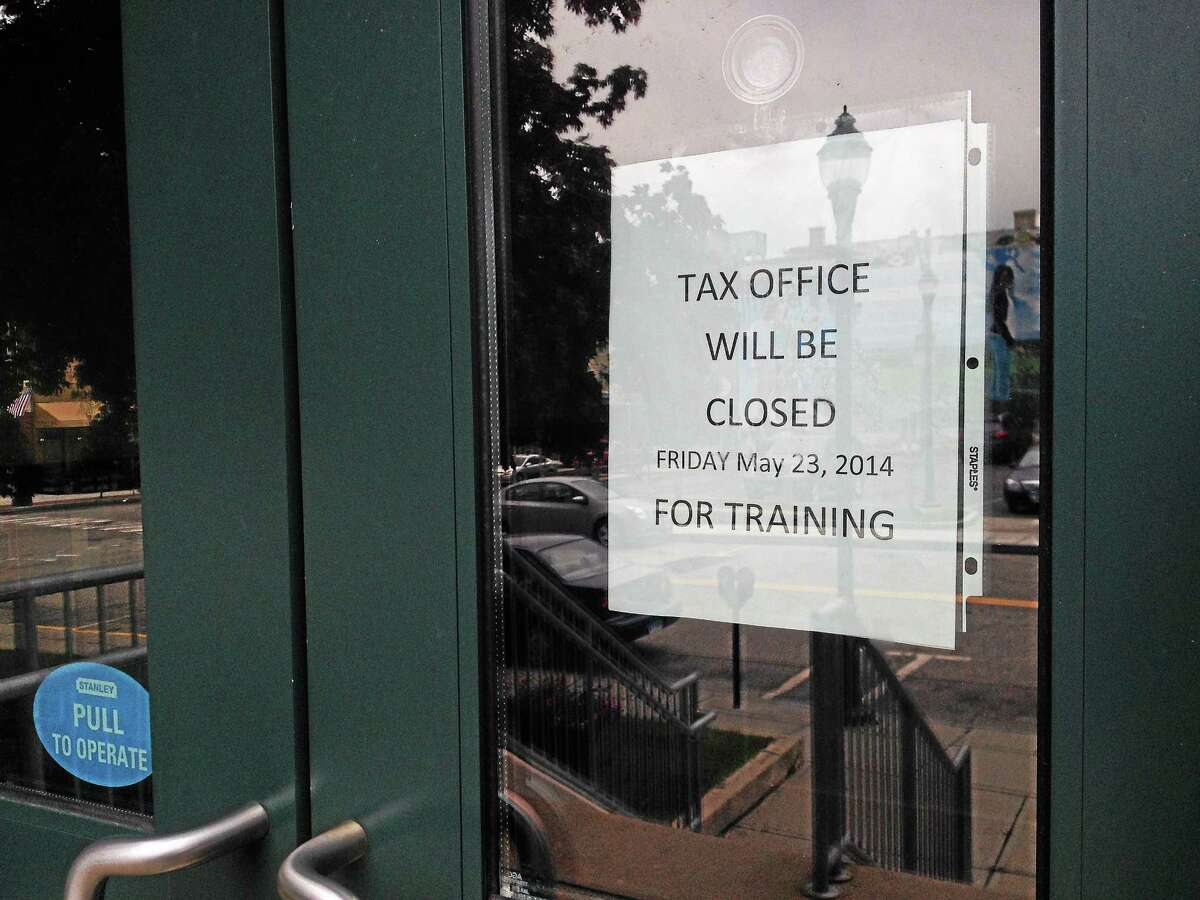 A sign outside city hall on Thursday, May 22, informs visitors that the Tax Collector's office will be closed on Friday for staff training.