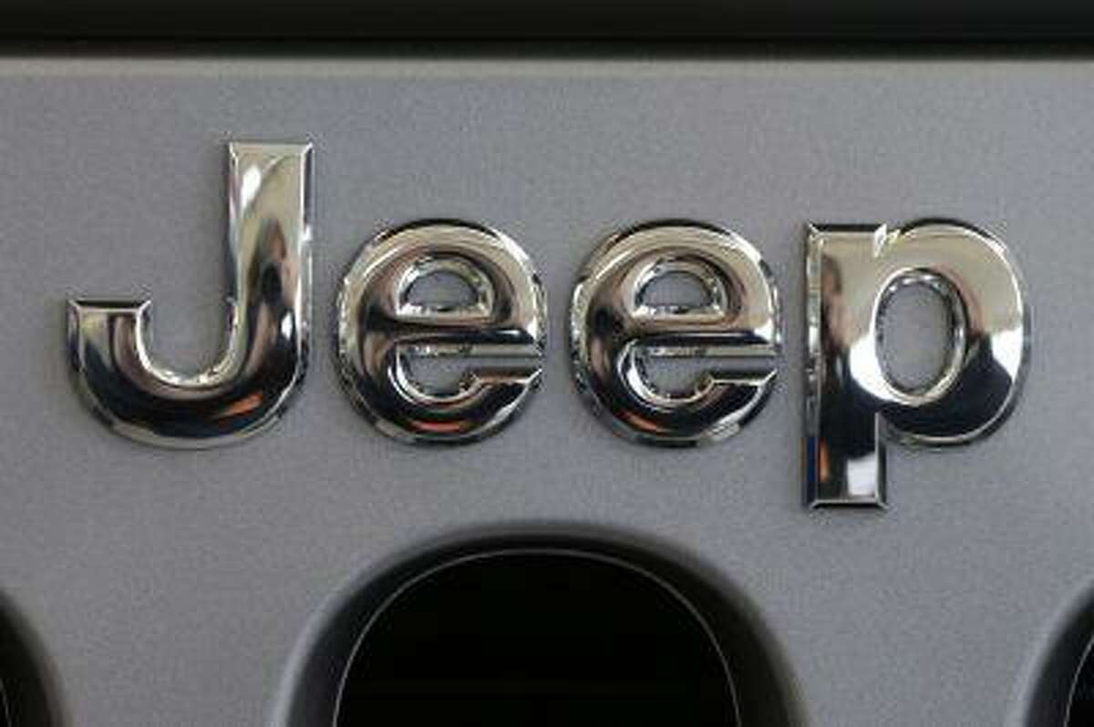 This Feb. 14, 2013 photo shows a Jeep logo on the grill of a Jeep Wrangler at the 2013 Pittsburgh Auto Show in Pittsburgh. Just two days after refusing a government request to recall 2.7 million older-model Jeeps, Chrysler has decided to do two other recalls totaling 630,000 vehicles worldwide, according to documents posted Thursday, June 6, 2013, on the National Highway Traffic Safety Administration website. The automaker will recall more than 409,000 Jeep Patriot and Compass small SUVs across the globe from the 2010 and 2012 model years to fix air bag and seat-belt problems. It's also recalling 221,000 Jeep Wranglers worldwide from 2012 and 2013 to fix transmission fluid leaks. (AP Photo/Gene J. Puskar)