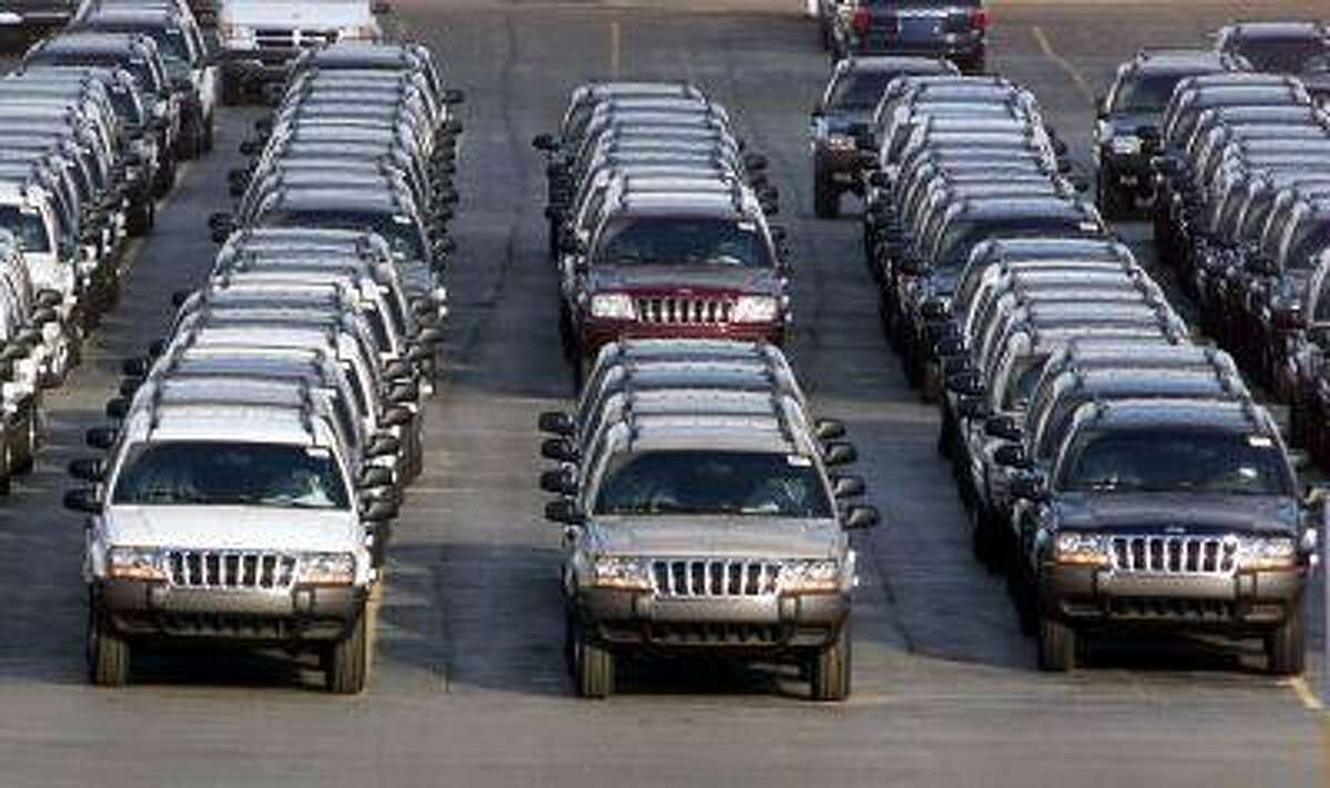 FILE - In this Feb. 2, 2001 file photo, rows of 2001 Jeep Grand Cherokees are lined up outside the Jefferson North Assembly Plant in Detroit. After an agreement between Chrysler and the U.S. government to remove about 1.2 million Jeep Grand Cherokees, model years 1999 to 2004, from a recall in June 2013, some owners are confused about the safety of their vehicles. Chrysler argued that those Jeeps have a different design than the ones it agreed to recall and are as safe as comparable models from other automakers. (AP Photo/Carlos Osorio, File)