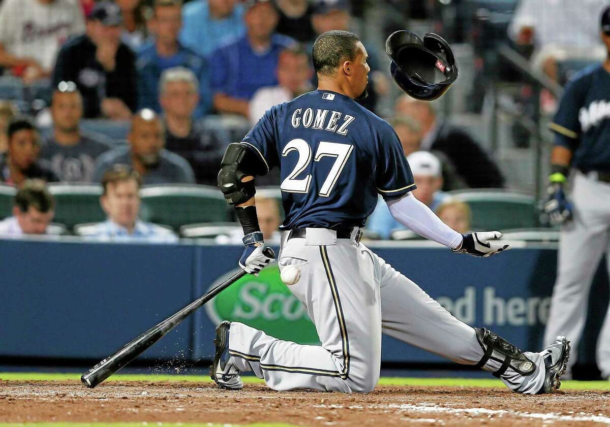 Milwaukee Brewers center fielder Carlos Gomez loses his helmet as he swings and misses during a game against the Braves on Monday in Atlanta.