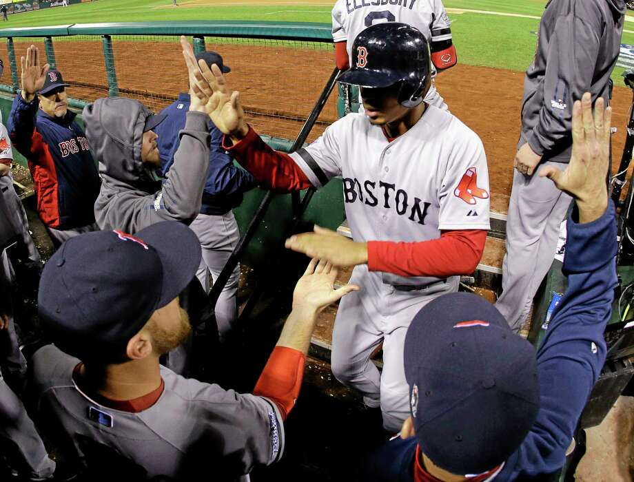 Boston Red Sox shortstop Xander Bogaerts is congratulated by teammates after scoring on a David Ross RBI ground-rule double against the Cardinals during the seventh inning of Game 5 of the World Series on Monday in St. Louis. Photo: Matt Slocum — The Associated Press  / AP