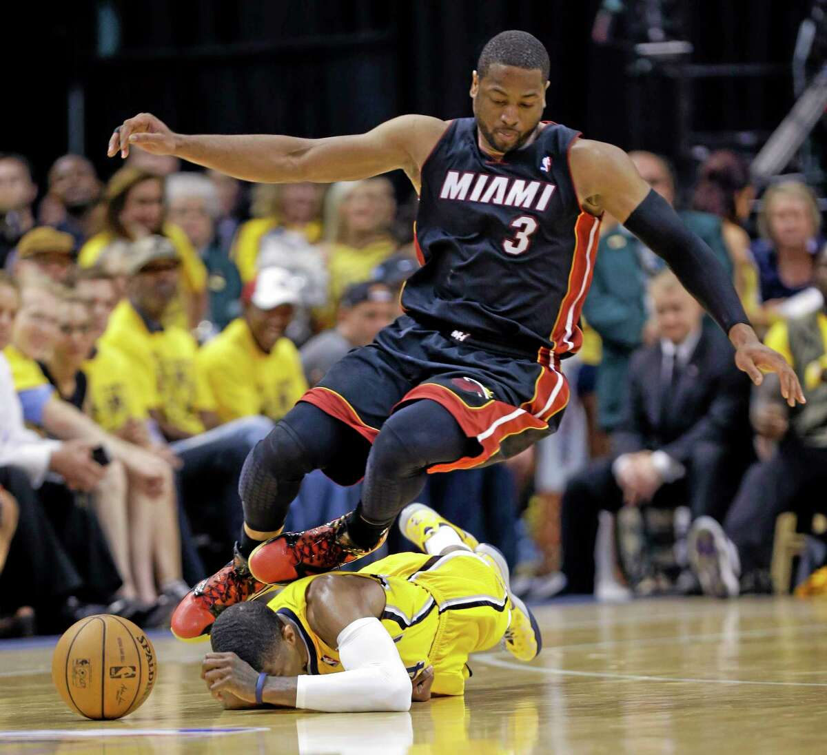 Miami Heat guard Dwyane Wade goes over Indiana Pacers forward Paul George as they go after a loose ball during the fourth quarter of Game 2 of the Eastern Conference finals Tuesday night in Indianapolis.