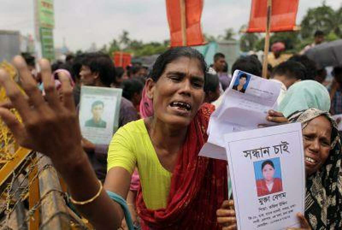 Bangladeshi women cry holding photographs of their missing relatives as they plead for help and demand compensation for the dead and missing workers of the garment factory building collapse, in Savar, near Dhaka, Bangladesh, Monday, June 24, 2013. Paper with a missing victim's photo, foreground at right, reads: