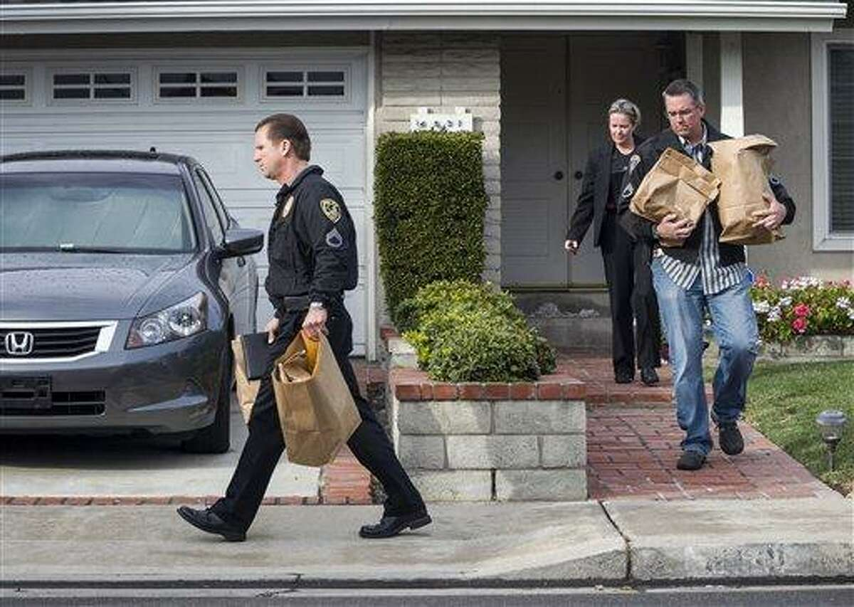 Police investigators take away evidence from the home of the mother of fugitive suspect former Los Angeles police officer Christopher Dorner, in La Palma, Calif. AP Photo/Damian Dovarganes