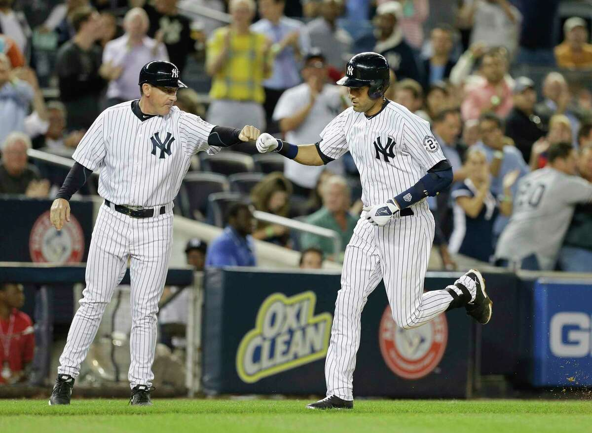 Derek Jeter bumps fists with third base coach Rob Thomson after hitting a home run during the sixth inning Thursday.