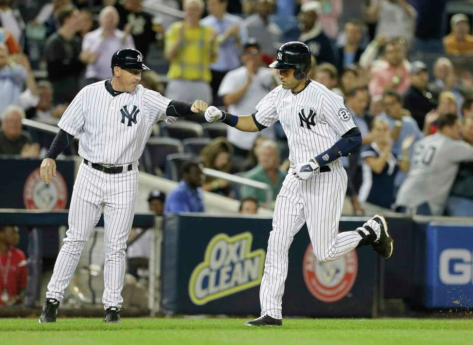 Derek Jeter bumps fists with third base coach Rob Thomson after hitting a home run during the sixth inning Thursday. Photo: Frank Franklin II — The Associated Press  / AP