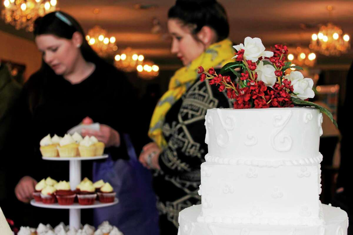 Guests at the Bridal Event at the Cornucopia Banquet Hall in Torrington look at cake samples on Sunday.