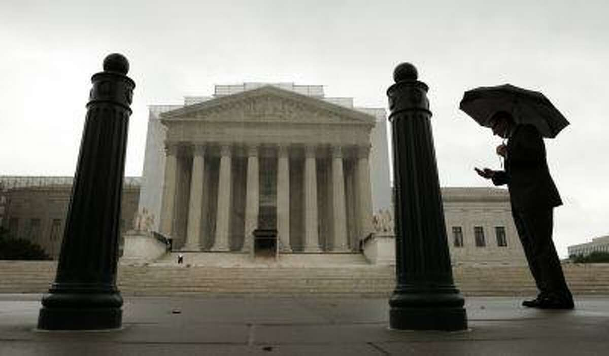 A man holds an umbrella outside the U..S. Supreme Court in Washington June 10, 2013.