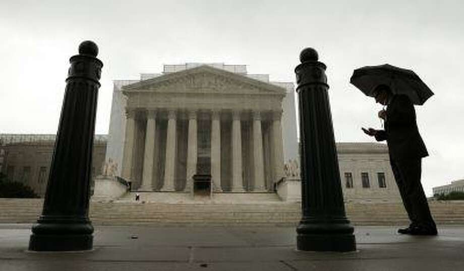 A man holds an umbrella outside the U..S. Supreme Court in Washington June 10, 2013. Photo: REUTERS / X00157