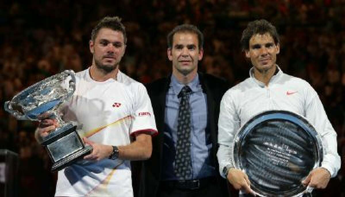 Stan Wawrinka of Switzerland, left, holds the trophy with runner-up Rafael Nadal of Spain, right, and former world No.1 Pete Sampras, after his win in their men's singles final at the Australian Open tennis championship in Melbourne, Australia, Sunday.