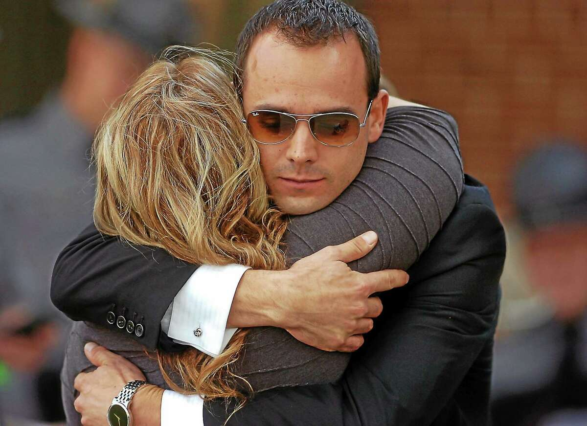 A man and woman embrace after leaving the Rotunda for the viewing of Pennsylvania State Trooper Cpl. Bryon Dickson on Sept. 17, 2014, at Marywood University in Scranton, Pa.