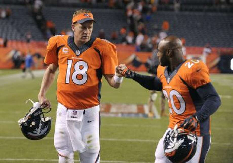 Denver Broncos quarterback Peyton Manning (18) bumps fists with strong safety Mike Adams (20) after beating the Oakland Raiders 37-21 in an NFL football game in Denver in September of 2013. Many thought his career was over at 37, with four surgical scars on his neck to match the four MVP awards in his trophy case, but a year later Denver's quarterback has led the Broncos to the Super Bowl and is in line for his fifth MVP award.