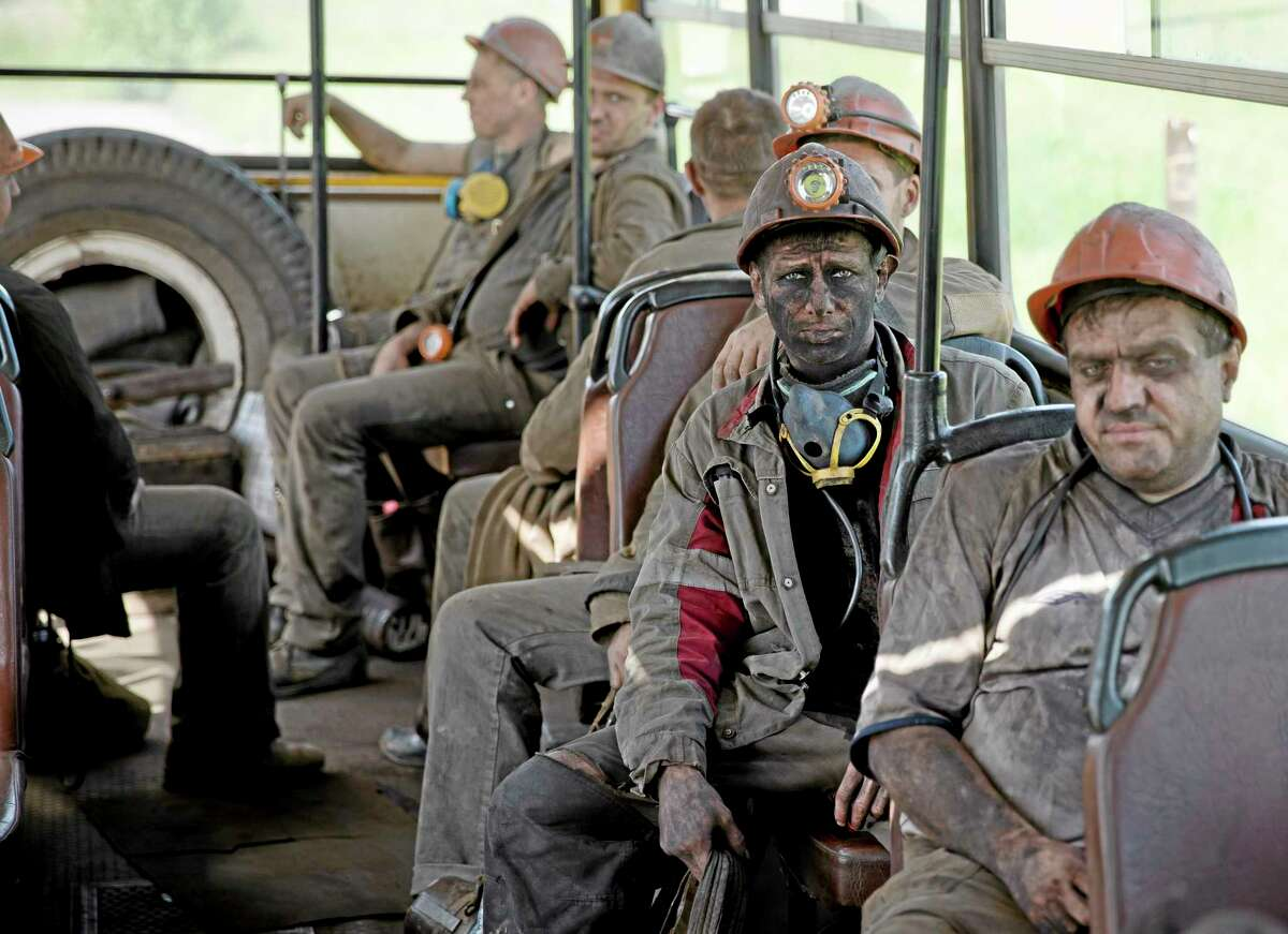 Ukrainian coal miners sit on a bus after finishing their shift at a coal mine outside Donetsk, Ukraine, Tuesday, May 20, 2014. While steel workers in Mariupol joined anti-separatist actions supported by the management of the plants, miners refused to take part in a planned protest against the Donetsk People's Republic. (AP Photo/Vadim Ghirda)