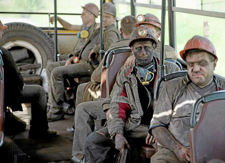 Ukrainian coal miners sit on a bus after finishing their shift at a coal mine outside Donetsk, Ukraine, Tuesday, May 20, 2014. While steel workers in Mariupol joined anti-separatist actions supported by the management of the plants, miners refused to take part in a planned protest against the Donetsk People's Republic. (AP Photo/Vadim Ghirda) Photo: AP / AP