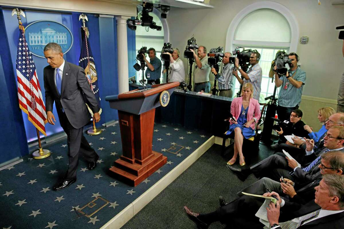 President Barack Obama leaves the podium after taking questions from reporters in the Brady Press Briefing Room of the White House in Washington, Wednesday, May 21, 2014, after he met with Veterans Affairs Secretary Eric Shinseki and Deputy Chief of Staff Rob Nabors. (AP Photo/Charles Dharapak)