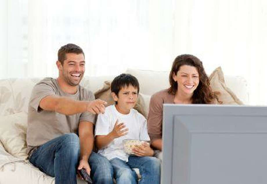 Family laughing while watching television together Photo: Getty Images/Wavebreak Media / Wavebreak Media