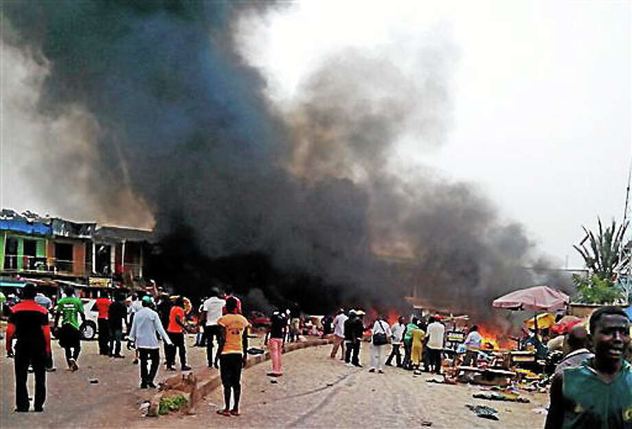 Smoke rises after a bomb blast at a bus terminal in Jos, Nigeria, Tuesday, May 20, 2014. Two explosions ripped through a bustling bus terminal and market frequented by thousands of people in Nigeria's central city of Jos on Tuesday afternoon, and police said there are an unknown number of casualties. The blasts could be heard miles away and clouds of black smoke rose above the city as firefighters and rescue workers struggled to reach the area as thousands of people fled. (AP Photo/Stefanos Foundation) Photo: AP / Stefanos Foundation