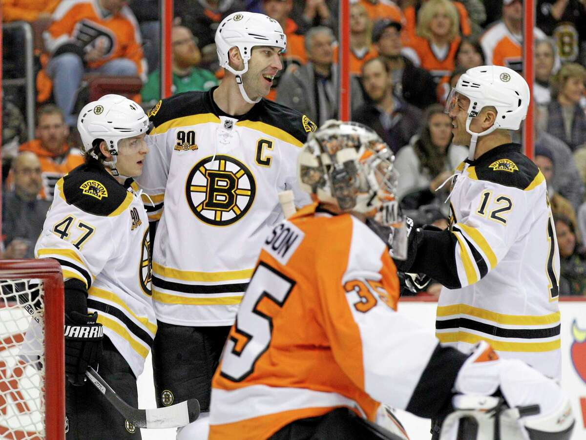 The Bruins' Zdeno Chara, top center, celebrates his power-play goal with Torey Krug, left, and Jarome Iginla as the Flyers' Steve Mason looks on during the first period of Boston's 6-1 win on Saturday in Philadelphia.