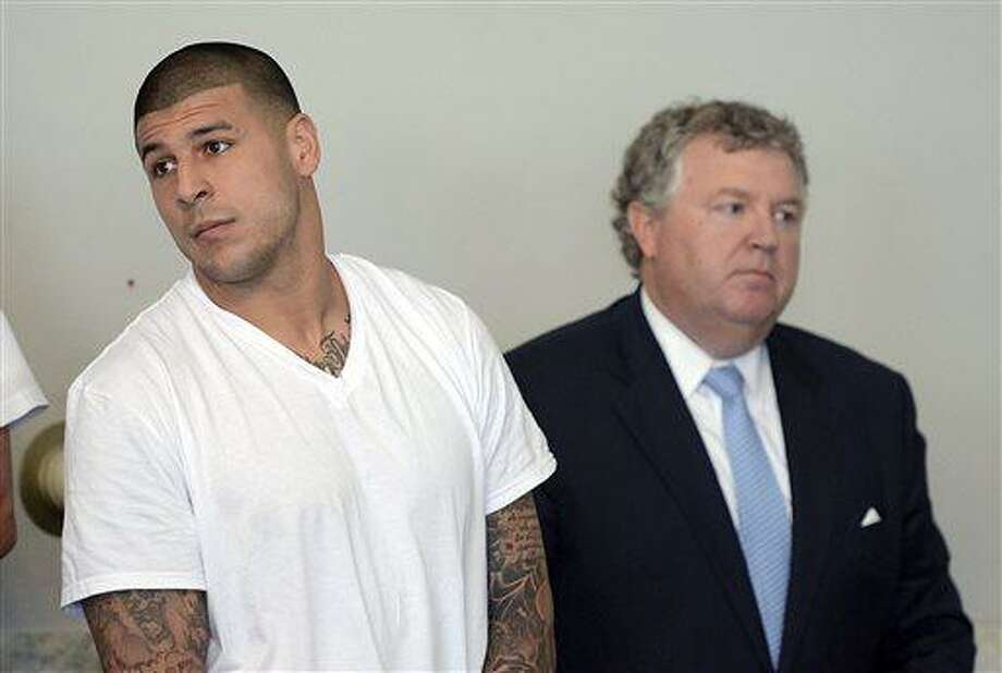 Former New England Patriots tight end Aaron Hernandez, left, stands with his attorney Michael Fee, right, during arraignment in Attleboro District Court Wednesday, June 26, in Attleboro, Mass. Hernandez was charged with murdering Odin Lloyd, a 27-year-old semi-pro football player for the Boston Bandits, whose body was found June 17 in an industrial park in North Attleborough, Mass.   (AP Photo/The Sun Chronicle, Mike George, Pool) Photo: AP / Pool, The Sun Chronicle
