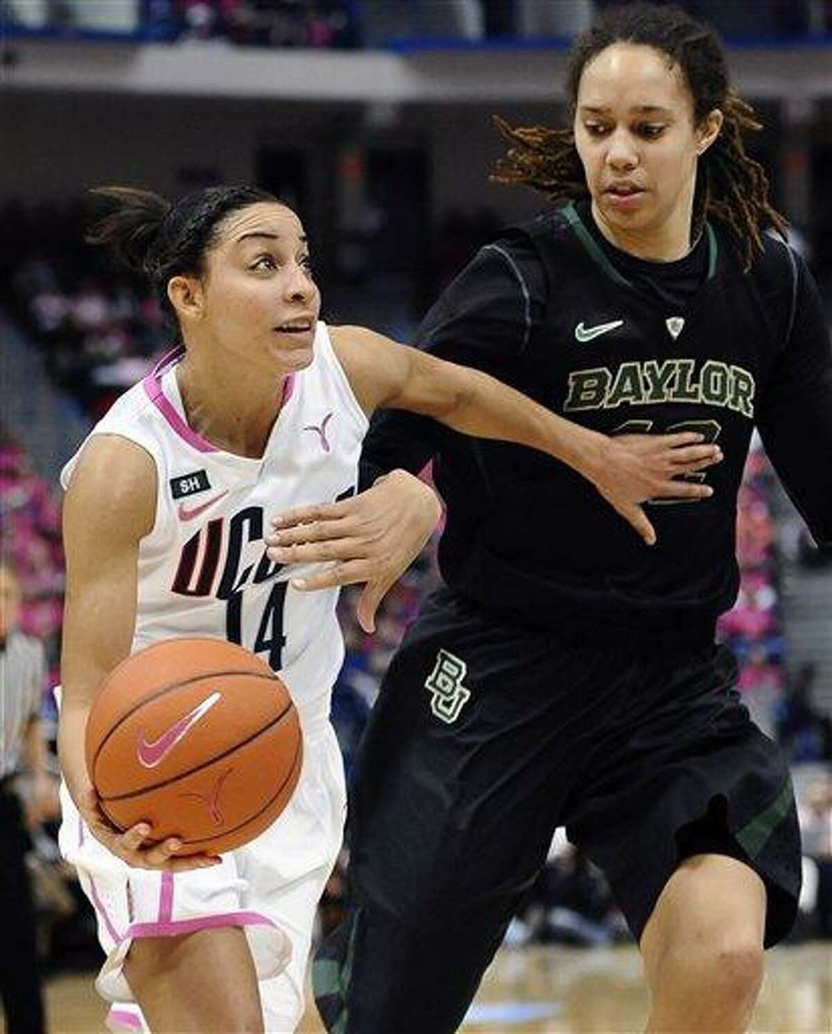 Connecticut's Bria Hartley, left, drives to the basket against Baylor's Brittney Griner during the first half of an NCAA college basketball game in Hartford, Conn., Monday, Feb. 18, 2013. (AP Photo/Jessica Hill)