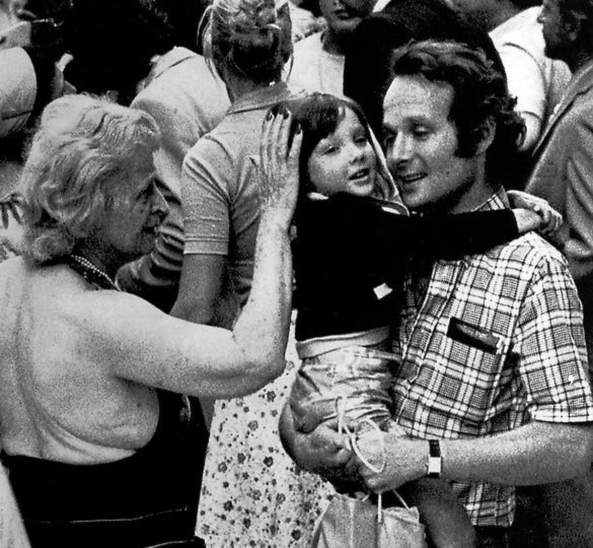 A father holds his daughter in his arms while a relative pats her head after the girl was flown to Orly Airport in Paris from Entebbe, Uganda, June 30, 1976. She was among 46 hostages released by Palestinian hijackers and flown to Paris in an Air France plane. (AP Photo)