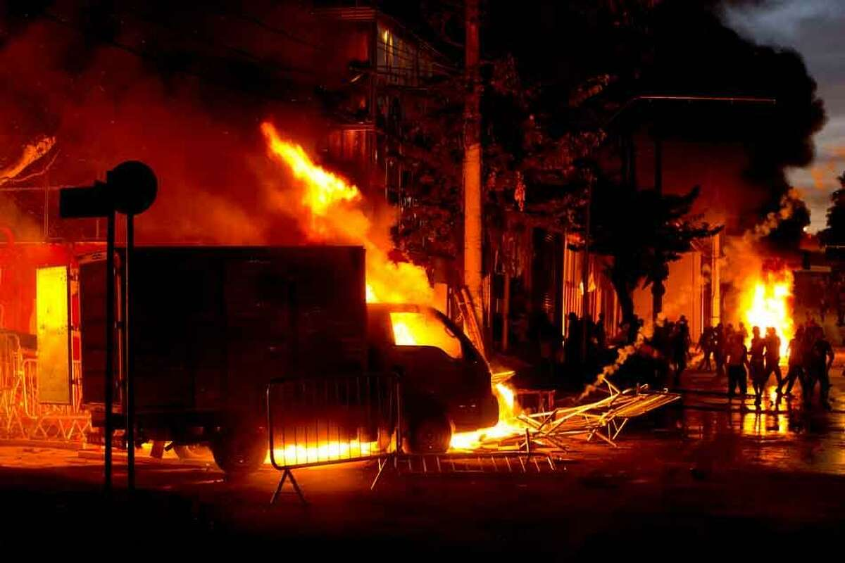 Protesters, right, set cars and stores on fire during a demonstration in Belo Horizonte, Brazil, Wednesday, June 26, 2013. Brazilian anti-government protesters in part angered by the billions spent in World Cup preparations and police clashed Wednesday near the stadium hosting a Confederations Cup football match, with tens of thousands of demonstrators trying to march on the site confronting police firing tear gas and rubber bullets. (AP Photo/Victor R. Caivano) (AP Photo/Victor R. Caivano)