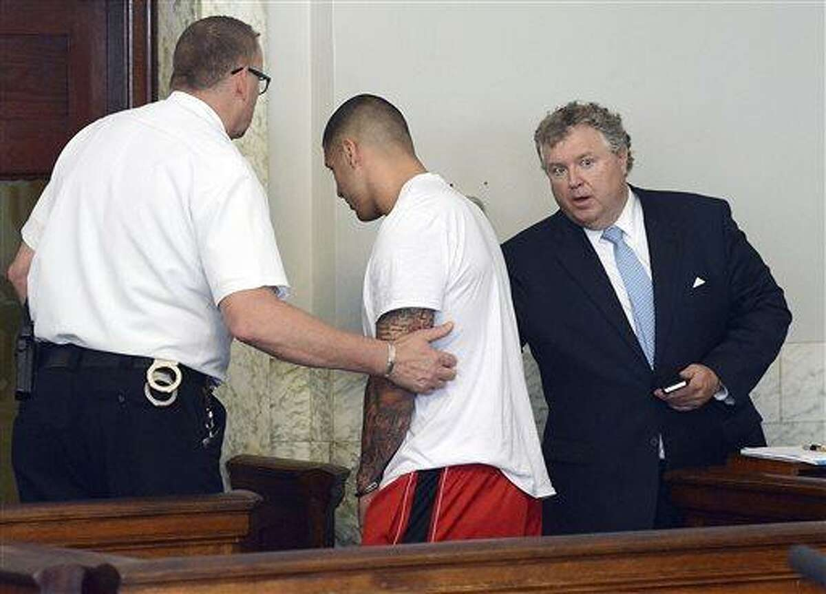 Former New England Patriots tight end Aaron Hernandez, center, is led away, as his attorney Michael Fee speaks to him, right, after arraignment in Attleboro District Court Wednesday, June 26, in Attleboro, Mass. Hernandez was charged with murdering Odin Lloyd, a 27-year-old semi-pro football player for the Boston Bandits, whose body was found June 17 in an industrial park in North Attleborough, Mass. (AP Photo/The Sun Chronicle, Mike George, Pool)