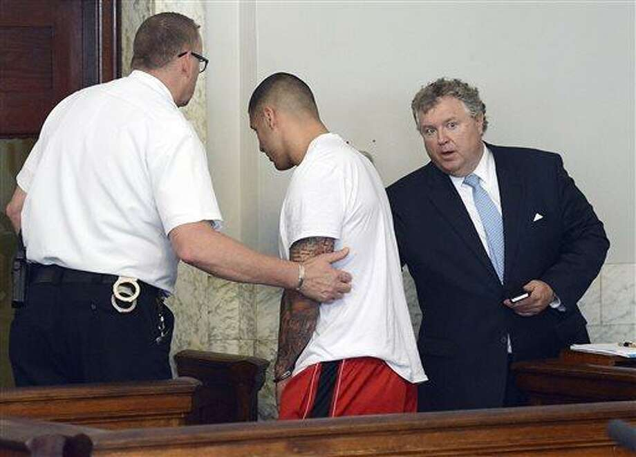 Former New England Patriots tight end Aaron Hernandez, center, is led away, as his attorney Michael Fee speaks to him, right, after arraignment in Attleboro District Court Wednesday, June 26, in Attleboro, Mass. Hernandez was charged with murdering Odin Lloyd, a 27-year-old semi-pro football player for the Boston Bandits, whose body was found June 17 in an industrial park in North Attleborough, Mass.   (AP Photo/The Sun Chronicle, Mike George, Pool) Photo: AP / Pool, The Sun Chronicle