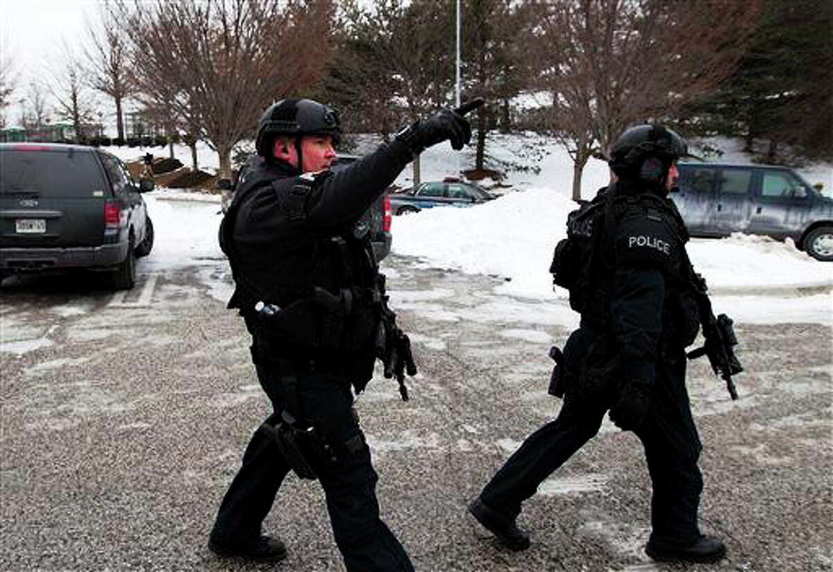 Police move in from a parking lot to the Mall in Columbia after reports of a multiple shooting, Saturday Jan. 25, 2014 Howard County, Md. Police in Maryland say three people died Saturday in a shooting at a mall in suburban Baltimore, including the presumed gunman.