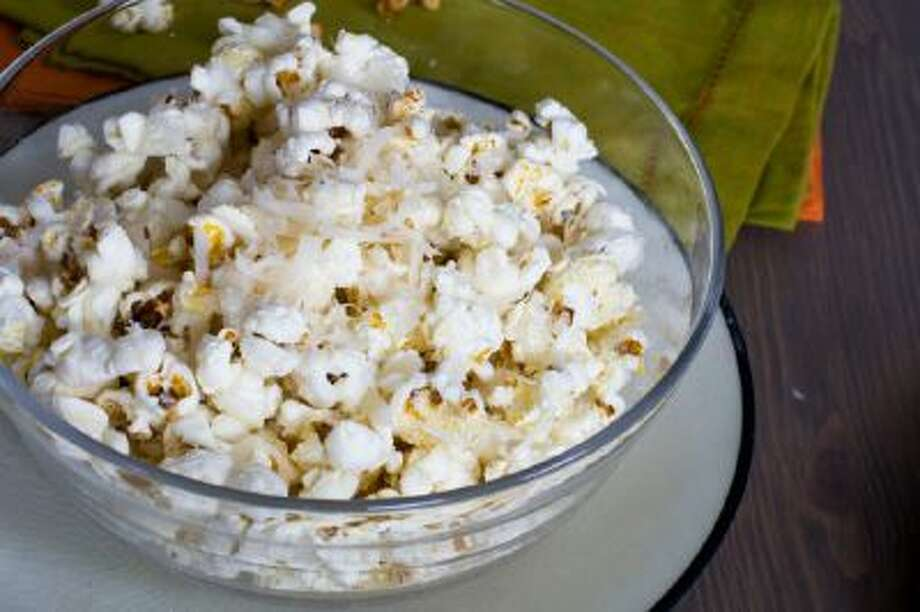 Popcorn with finely grated parmesan cheese is shown served in a bowl.