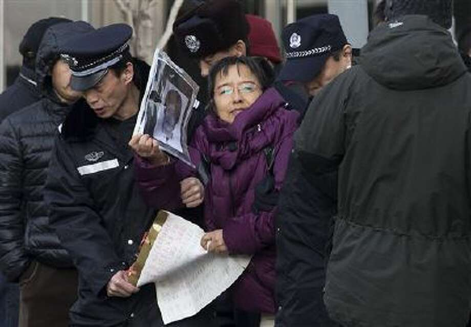 A demonstrator is detained by policemen while she gathers with other supporters near the Beijing's No. 1 Intermediate People's Court. Photo: AP / AP