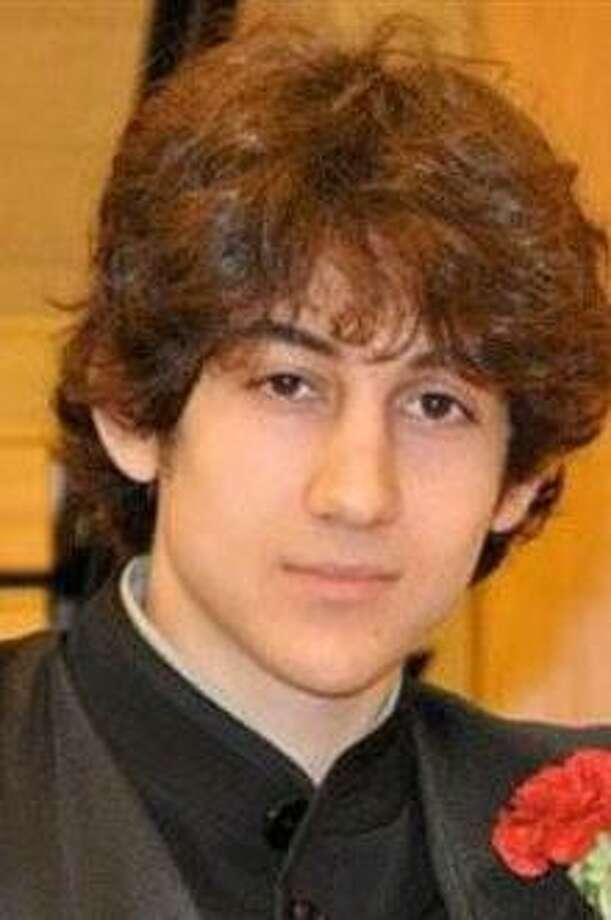 In this undated photo provided by Robin Young, Dzhokhar A. Tsarnaev poses for a photo after graduating from Cambridge Rindge and Latin High School. Tsarnaev has been identified as the surviving suspect in the marathon bombings. Two suspects in the Boston Marathon bombing killed an MIT police officer, injured a transit officer in a firefight and threw explosive devices at police during a getaway attempt in a long night of violence that left one of them dead and another still at large Friday, April 19, 2013. (AP Photo/Robin Young) Photo: AP / Here And Now