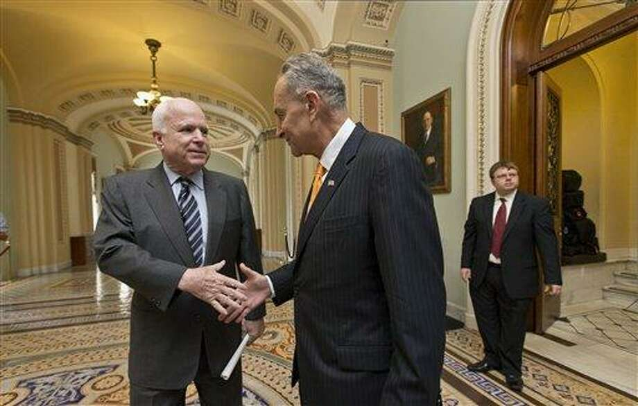 "Sen. John McCain, R-Ariz., left, and Sen. Charles Schumer, D-N.Y., right, two of the authors of the immigration reform bill crafted by the Senate's bipartisan ""Gang of Eight,"" shakes hands on Capitol Hill in Washington, Thursday, June 27, 2013, prior to the final vote. The historic legislation would dramatically remake the U.S. immigration system and require a tough new focus on border security.  (AP Photo/J. Scott Applewhite) Photo: AP / AP"