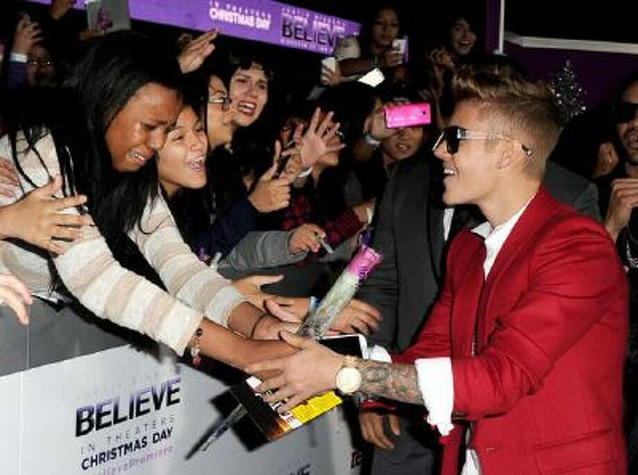 """Singer Justin Bieber arrives at the premiere of Open Road Films' """"Justin Bieber's Believe"""" at the Regal Cinemas L.A. Live on December 18, 2013 in Los Angeles, California."""