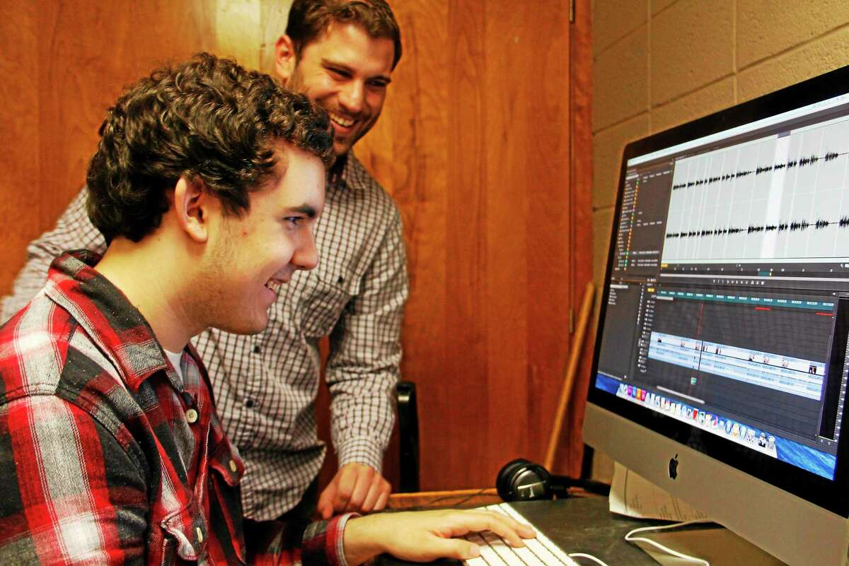Torrington High School sophomore Evan Dunlap (seated) laughs as he gets some editing advice from Benjamin Willis of the Civic Life Project on Wednesday, May 21, 2014, in Torrington. Register Citizen Esteban L. Hernandez