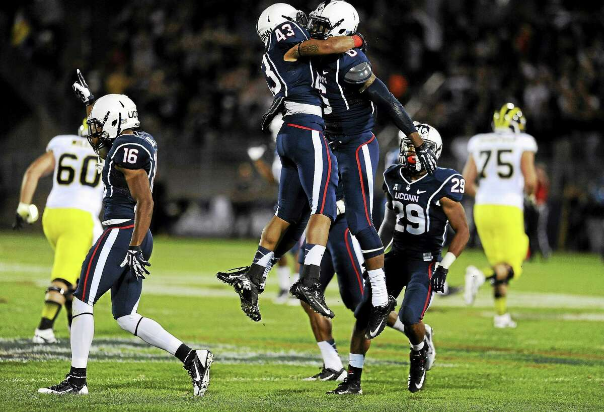 UConn cornerback Jhavon Williams celebrates with running back Lyle McCombs (43) after intercepting a pass against Michigan last September at Rentschler Field in East Hartford.