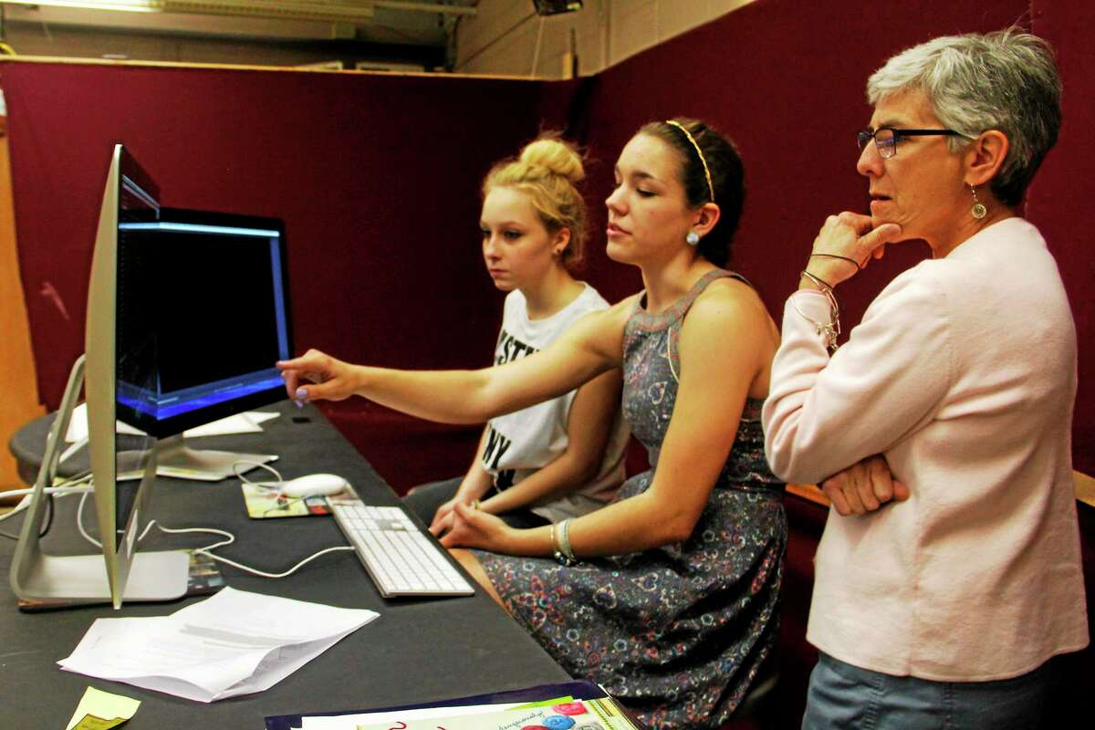 From left: Torrington High School sophomores Marielle Franco and Elizabeth Garcia discuss editing a documentary with adviser and schools library media specialist Robin Magistrali on Wednesday, May 21, 2014, in Torrington. The students are in a technology class called ìCitizenship and Actionî and are part of an 18-student class producing two documentaries. Register Citizen Esteban L. Hernandez